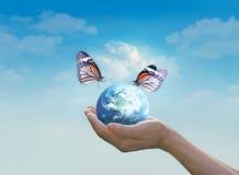 Mulher que guarda a terra do planeta com a borboleta nas mãos no fundo limpo do céu azul Foto de Stock