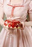 Mulher que guarda a torta da morango no suporte do bolo Foto de Stock Royalty Free