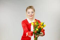 Mulher que guarda tulipas e presente Foto de Stock Royalty Free