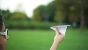Mulher que guarda um avião de papel no parque vídeos de arquivo