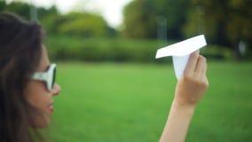 Mulher que guarda um avião de papel no parque video estoque