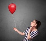 Mulher que guarda um balão vermelho Foto de Stock Royalty Free