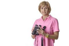 Mulher que guarda um binocular em suas mãos Fotografia de Stock Royalty Free