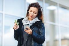 Mulher que guarda um cartão de crédito e que usa o telefone celular para a compra em linha Fotografia de Stock Royalty Free
