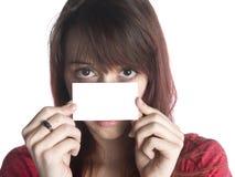 Mulher que guarda um cartão vazio perto de sua cara Fotos de Stock Royalty Free