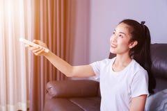 Mulher que guarda um condicionador de ar de controle remoto no sofá em casa fotos de stock royalty free