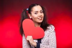 Mulher que guarda um coração vermelho do papper nas mãos Imagens de Stock