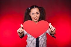 Mulher que guarda um coração vermelho do papper nas mãos Fotografia de Stock Royalty Free