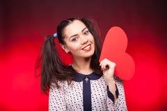 Mulher que guarda um coração vermelho do papper nas mãos Fotografia de Stock