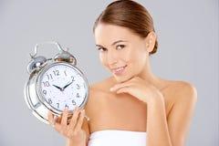 Mulher que guarda um despertador Imagem de Stock Royalty Free