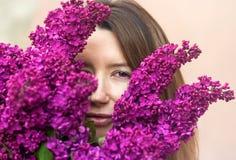 Mulher que guarda um grande ramalhete de flores lilás perto acima imagem de stock