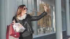 Mulher que guarda um grupo dos sacos de compras que fazem Selfie na rua filme