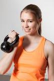 Mulher que guarda um kettlebell e que sorri à câmera - fitn do crossfit Imagens de Stock