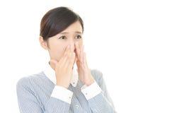 A mulher que guarda um nariz na verificação imagens de stock royalty free