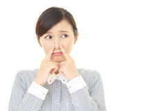 A mulher que guarda um nariz na verificação imagem de stock royalty free