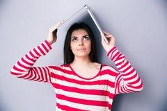 A mulher que guarda um portátil acima de sua cabeça gosta de um telhado Imagens de Stock
