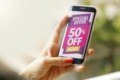 Mulher que guarda um smartphone com uma propaganda do disconto de 50% na tela Foto de Stock Royalty Free