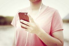 Mulher que guarda um smartphone que escuta a música Fotografia de Stock Royalty Free