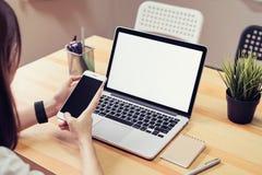 Mulher que guarda um telefone de tela vazia e um portátil e posta um relógio esperto fotografia de stock