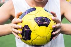Mulher que guarda uma bola de futebol em suas mãos Imagens de Stock Royalty Free