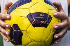 Mulher que guarda uma bola de futebol em suas mãos Fotos de Stock