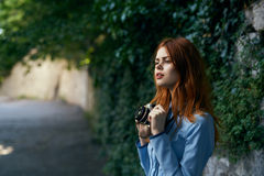 Mulher que guarda uma câmera na rua imagem de stock