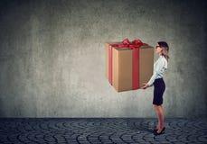 Mulher que guarda uma caixa de presente atual grande foto de stock royalty free