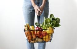 Mulher que guarda uma cesta dos frutos & dos vegetais imagem de stock
