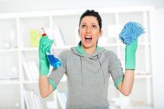 Mulher que guarda uma esponja e um pulverizador para limpar Imagem de Stock
