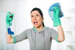 Mulher que guarda uma esponja e um pulverizador para limpar Imagens de Stock