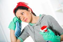 Mulher que guarda uma esponja e um pulverizador para limpar Fotos de Stock