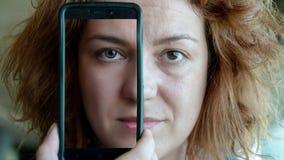 Mulher que guarda uma metade da coberta do smartphone de sua cara, th da exibição vídeos de arquivo