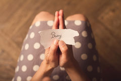 A mulher que guarda uma nota de papel com o texto reza Fotografia de Stock