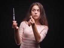 Mulher que guarda uma seringa e um topete do cabelo em um fundo preto Sintomas do apego e da doença Conceito do tratamento do cab Fotografia de Stock