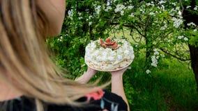 Mulher que guarda uma torta de creme em exterior imagens de stock royalty free