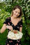 Mulher que guarda uma torta de creme em exterior imagem de stock