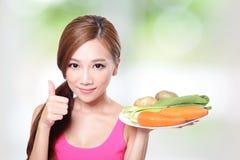 Mulher que guarda vegetais e cenouras verdes Fotografia de Stock Royalty Free