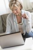 Mulher que guarda vidros ao usar o portátil fotos de stock royalty free