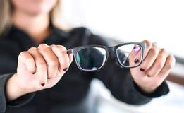 Mulher que guarda vidros novos Lentes e espetáculos que obtêm o reparo e o reparo pelo ótico profissional fotos de stock