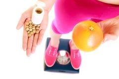 Mulher que guarda vitaminas e maçã Cuidados médicos Foto de Stock
