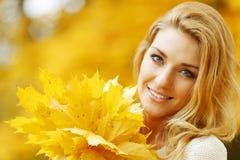 Mulher que guardara as folhas de outono fotos de stock
