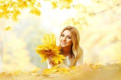 Mulher que guardara as folhas de outono fotos de stock royalty free