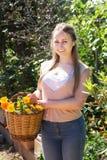 Mulher que guardara a cesta com flores Imagem de Stock