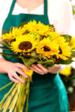 Mulher que guardara a flor do amarelo do florista dos girassóis do ramalhete Fotos de Stock Royalty Free