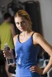 Mulher que guardara a garrafa de água no health club Imagens de Stock