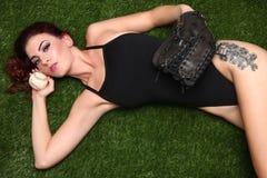 A mulher que guardara o basebol ostenta a engrenagem na grama Fotografia de Stock Royalty Free