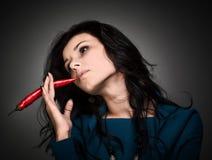 Mulher que guardara a pimenta de pimentão encarnado na boca Imagem de Stock