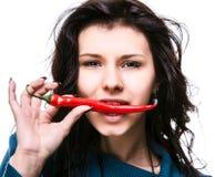 Mulher que guardara a pimenta de pimentão encarnado na boca Fotografia de Stock Royalty Free
