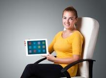 Mulher que guardara a tabuleta moderna com ícones coloridos Fotografia de Stock
