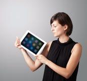 Mulher que guardara a tabuleta moderna com ícones coloridos Imagem de Stock Royalty Free
